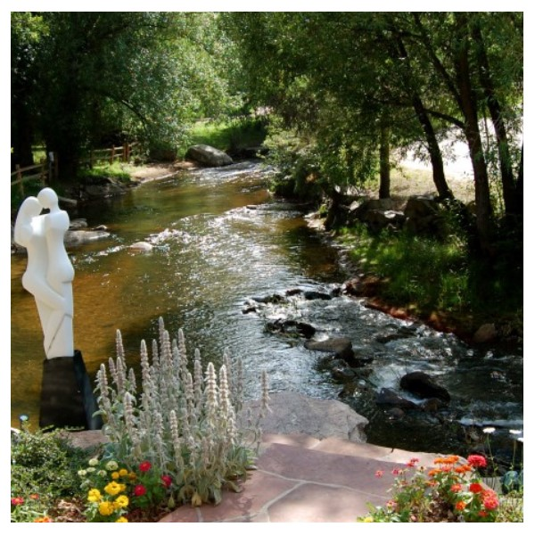 Picture of a river with flowers and sculpture
